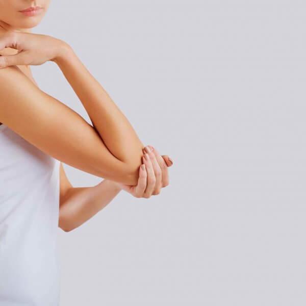 Frau beugt Hand und fasst sich an den Ellenbogen Orthopädie Rosenheim