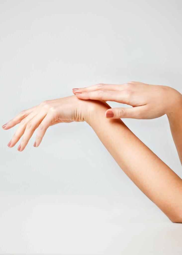 Damenhand streichelt über Handrücken zweiter Hand Orthopäde Rosenheim