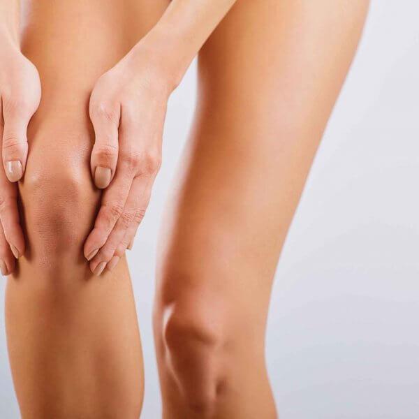 Nahansicht Frauenhände fassen an Knie Orthopädie Rosenheim