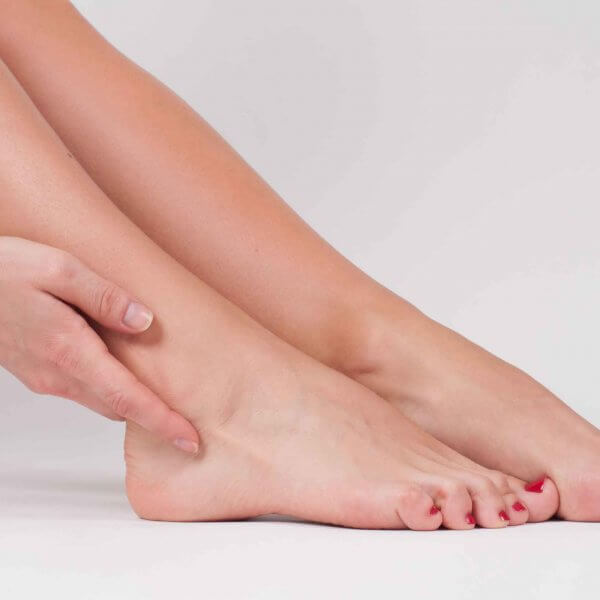 Nahansicht Frauenhände Griff an Sprunggelenk Orthopädie Rosenheim