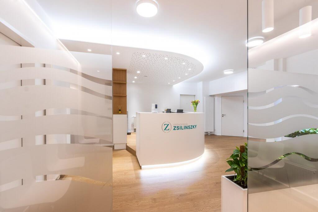 Blick durch geöffnete Tür auf Empfangstresen der Orthopädie Zsilinszky in Rosenheim