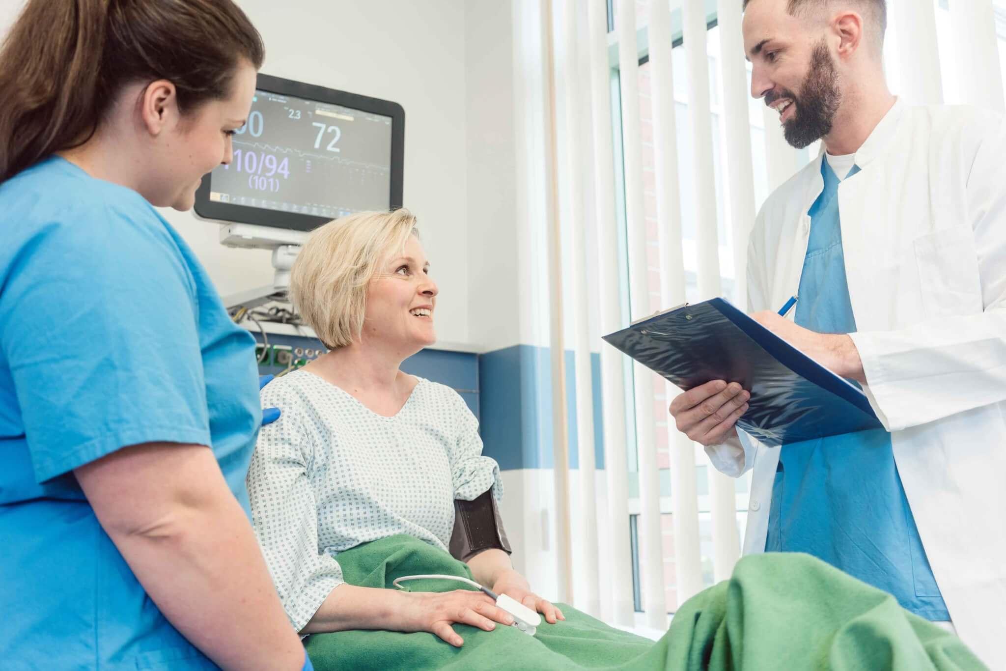 Patientin im Krankenhaus im Gespräch mit Arzt und Krankenschwester
