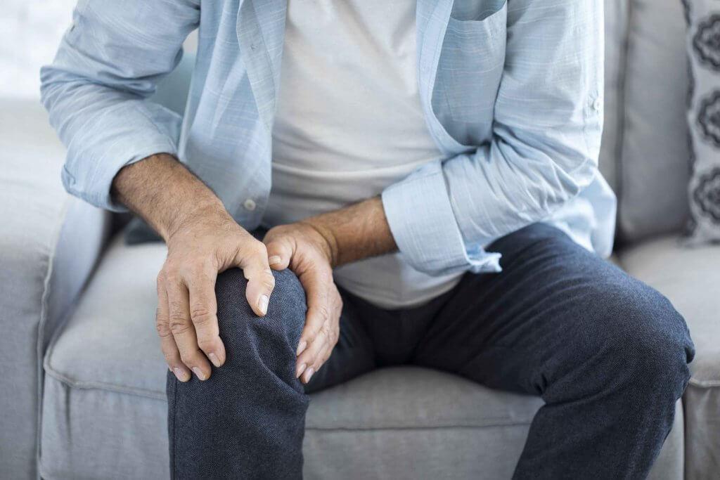 Sitzender Mann auf Couch mit Griff an Knie Arthrose