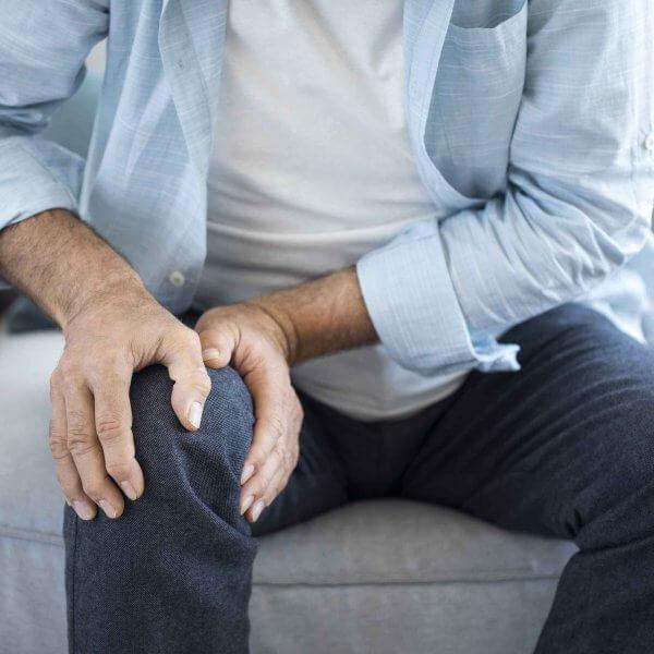 Sitzender Mann auf Couch hält Knie Arthrose Orthopädie Rosenheim