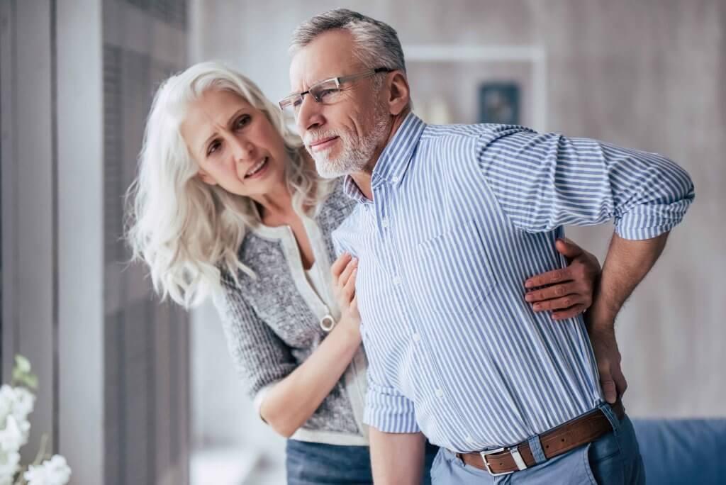 Ältere Frau stützt Partner mit Rückenschmerzen