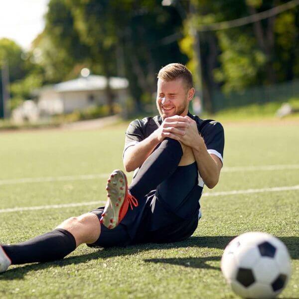 Spieler auf Fußballfeld umfasst Knie wegen Sportverletzung